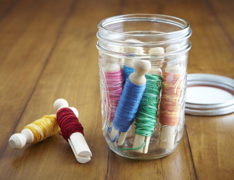 Craft threads in a mason jar on wood