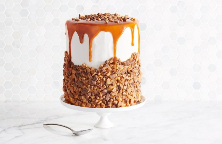A tall cake drizzled and covered in caramel and nuts