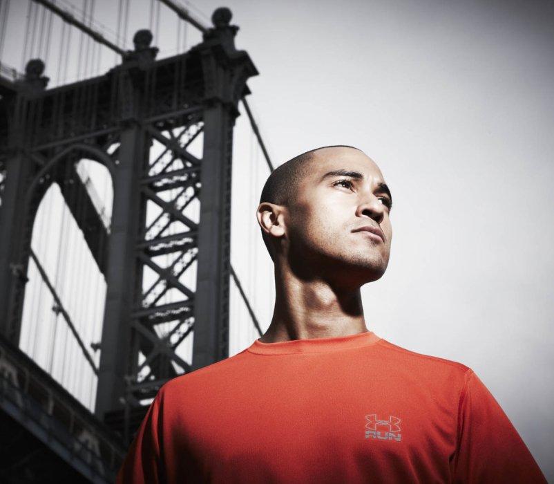 Proud athlete portrait with bridge background wearing an orange shirt
