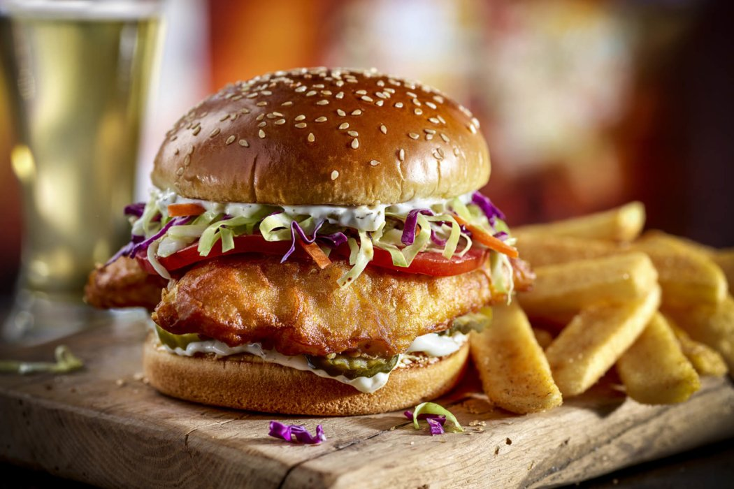 A fried fish sandwich with fries