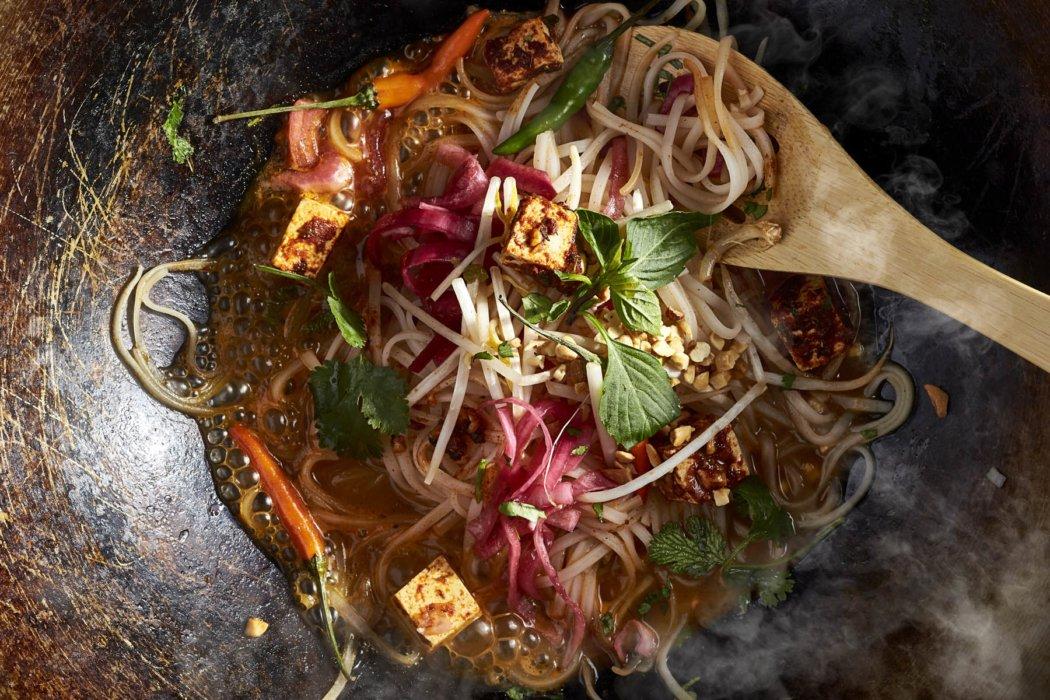 A noodle and tofu dish prepared in a wok