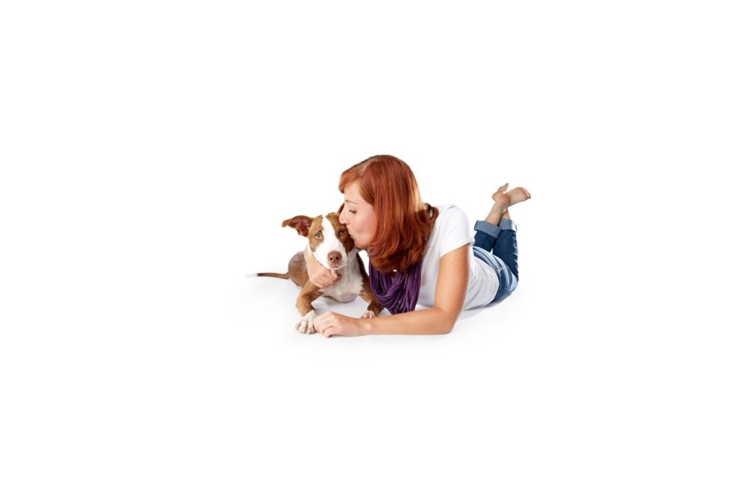 Dog and owner laying on a white background
