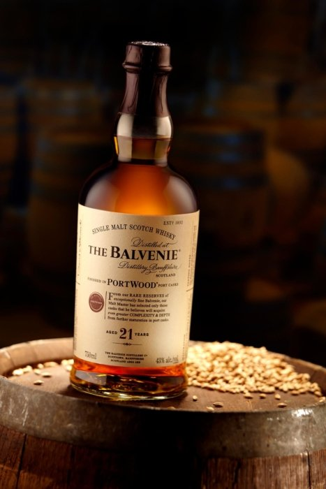 The Balvenie liquor bottle on a barrel with a dark background