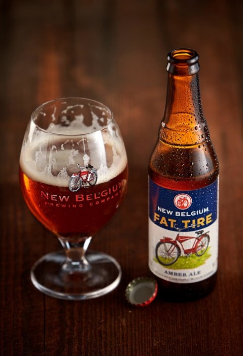 New Belgium Fat Tire brown bottle beer poured in a glass with some head