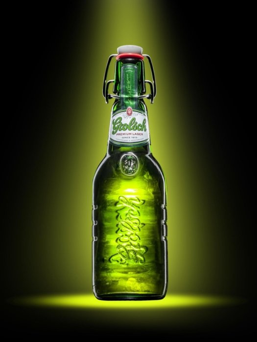 Grolsch lager in a green beer bottle on a green lit background