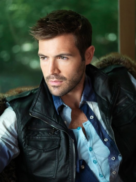 A male fashion model outside wearing a leather vest
