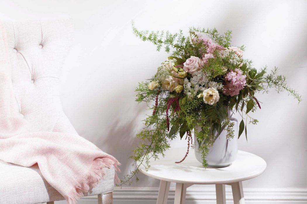 A fern and flower arrangement on a white end table next to a chair