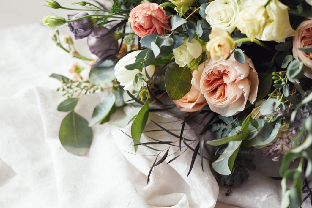 A close up of flowers on a white table cloth