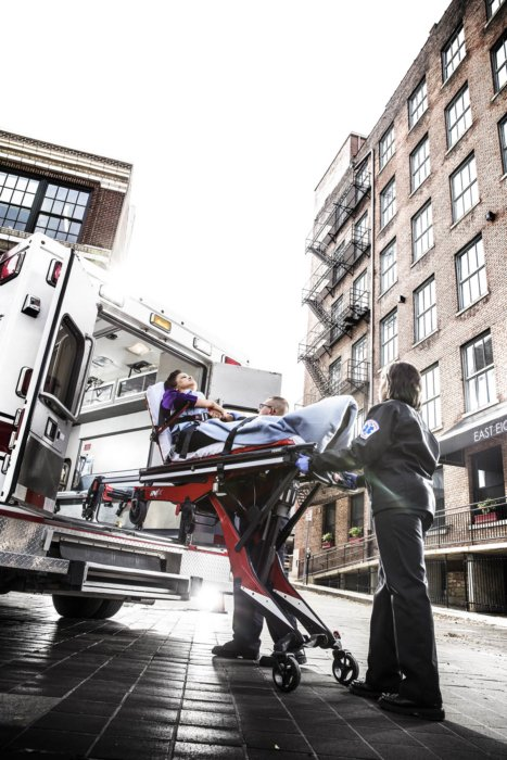 An ambulance and EMTS in a city scene