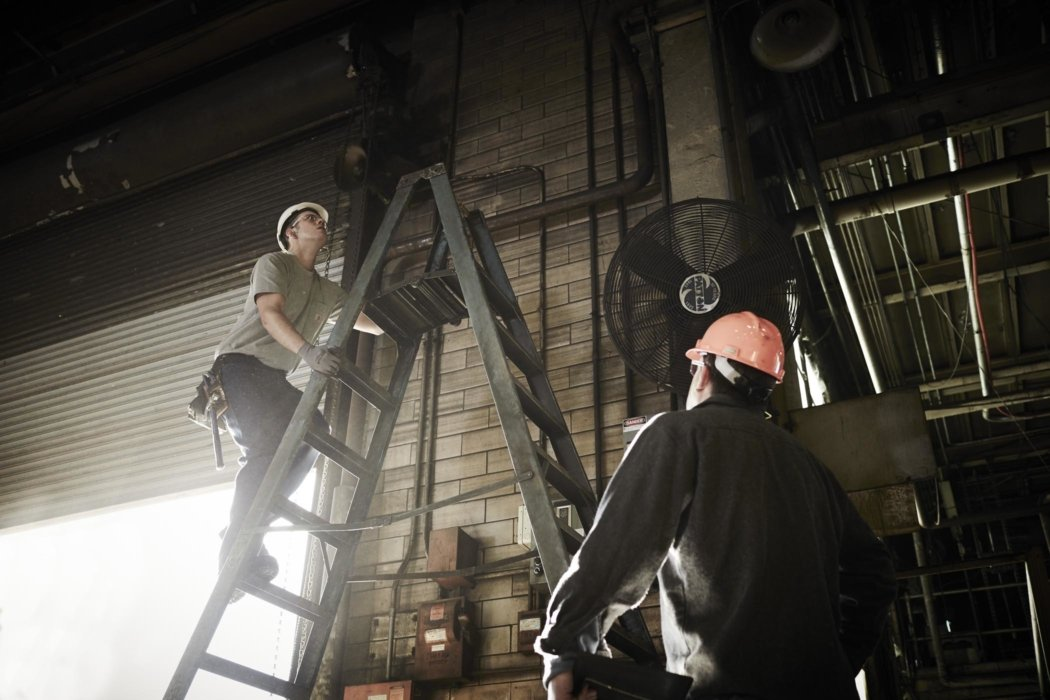 Industrial workers on a ladder