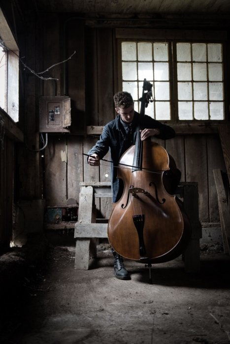 A man playing a cello in a old building