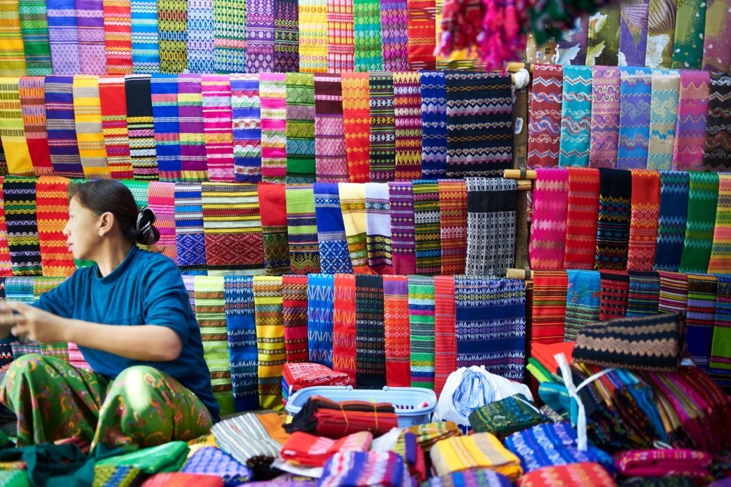 Travel photo of woman selling textiles