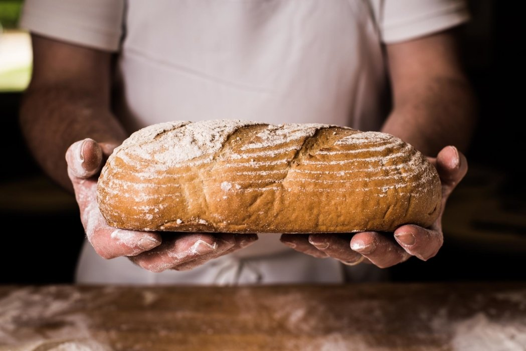 Fresh baked artisan bread being held with hands