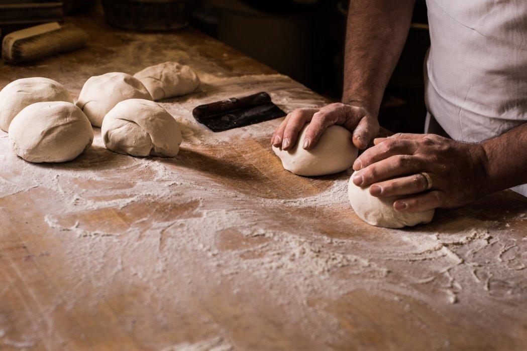 Preparing raw bread dough balls for baking