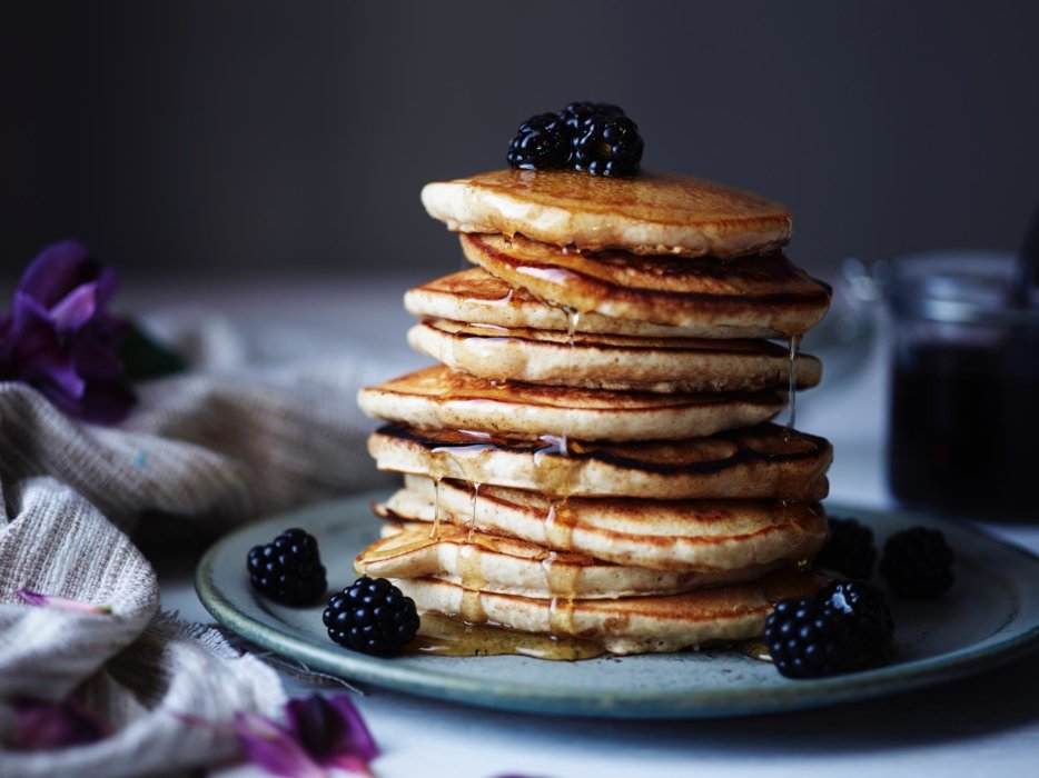 A stack of pancakes with blackberries