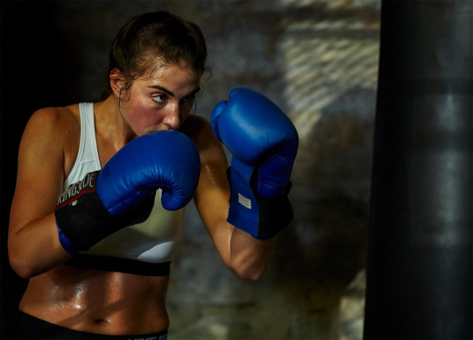 Female boxing athlete hitting a punching bag