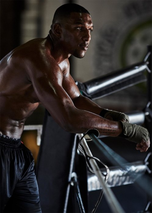 Male boxing athlete leaning on ropes