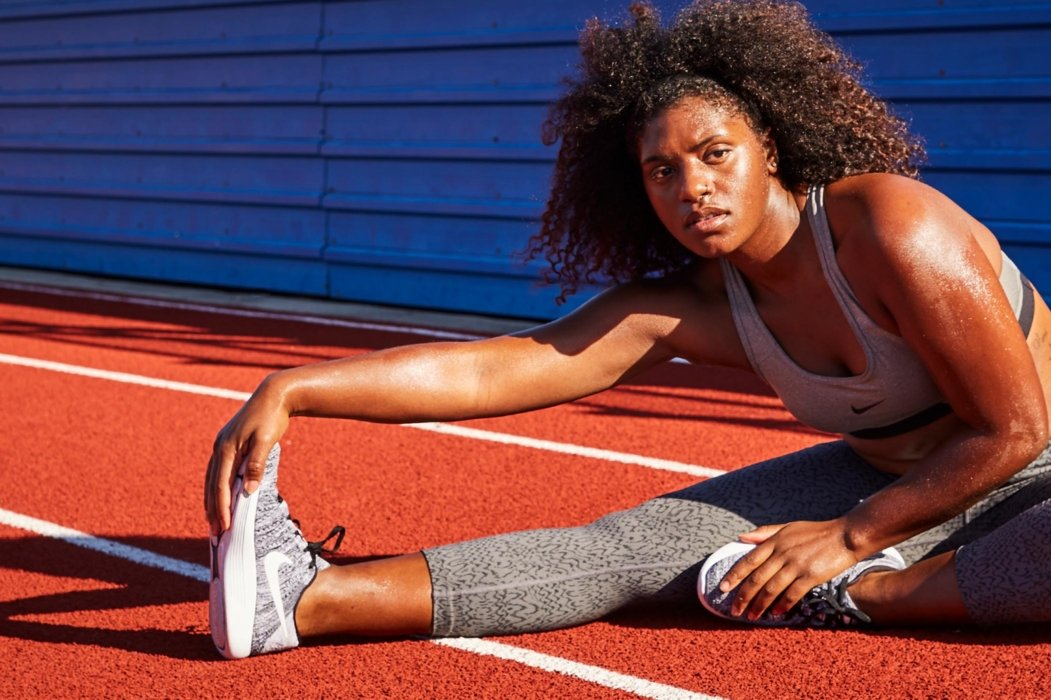 Female athlete portrait stretching with Nike shoes
