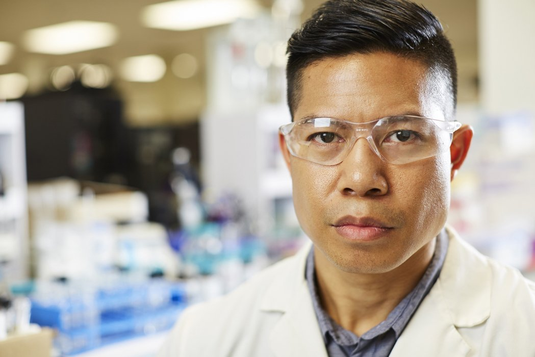 A close up of a man in a lab coat with glasses
