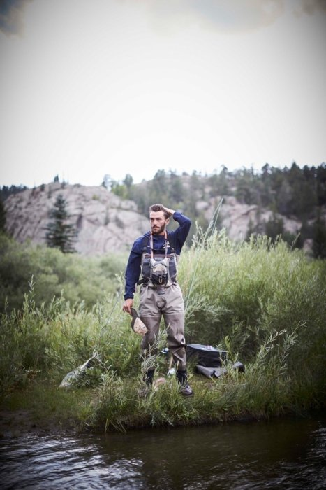 Man standing at river in outdoor gear - lifestyle photography