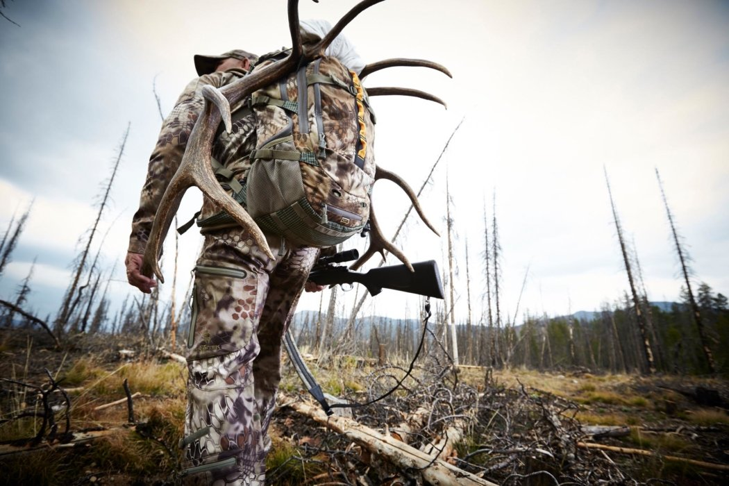 A hunter walking with outdoor equipment