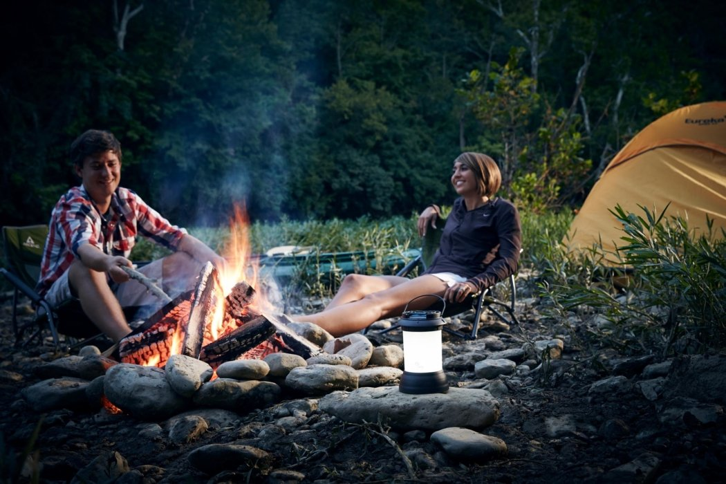 People camping with camping equipment having a fire - lifestyle photography