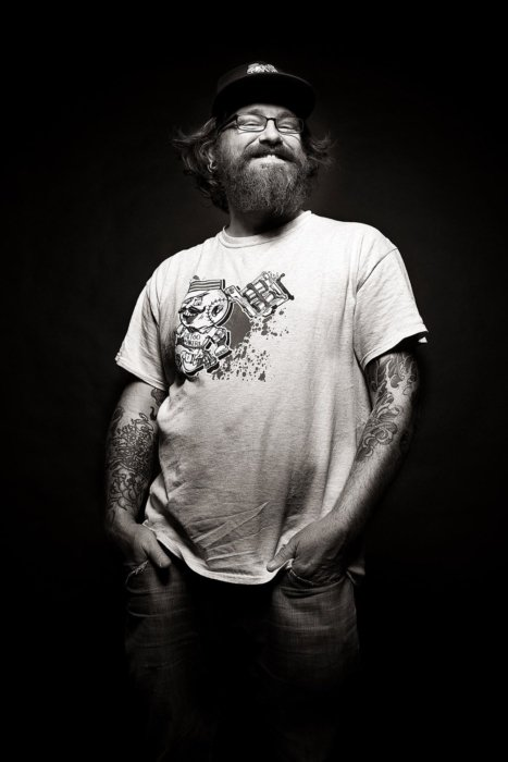 Portrait of a bearded man on black background with hands in pocket