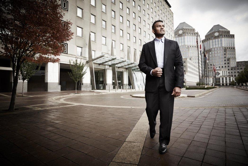 A man walking outside near corporate buildings