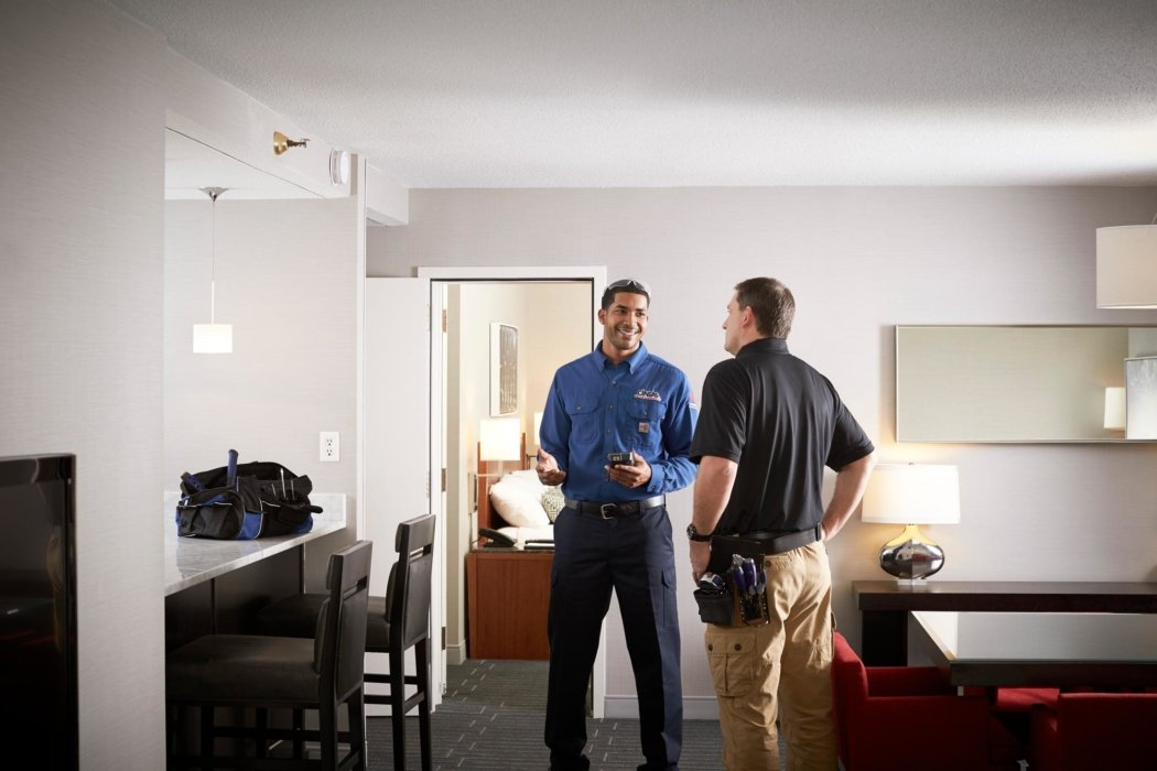 Two workers working in a hotel room