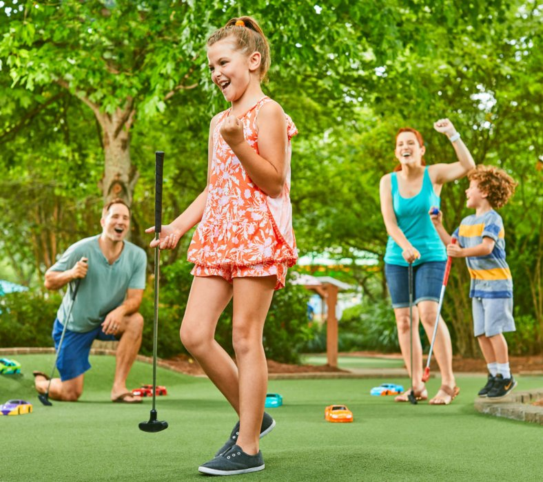 A girl and family nailing a put put golf shot - lifestyle photography