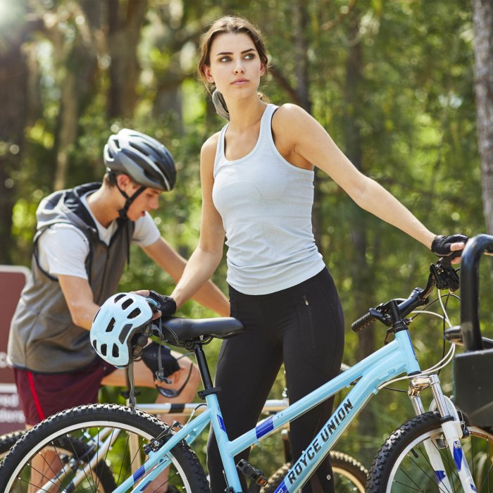 A young yclist getting her bike ready for a ride in the woods