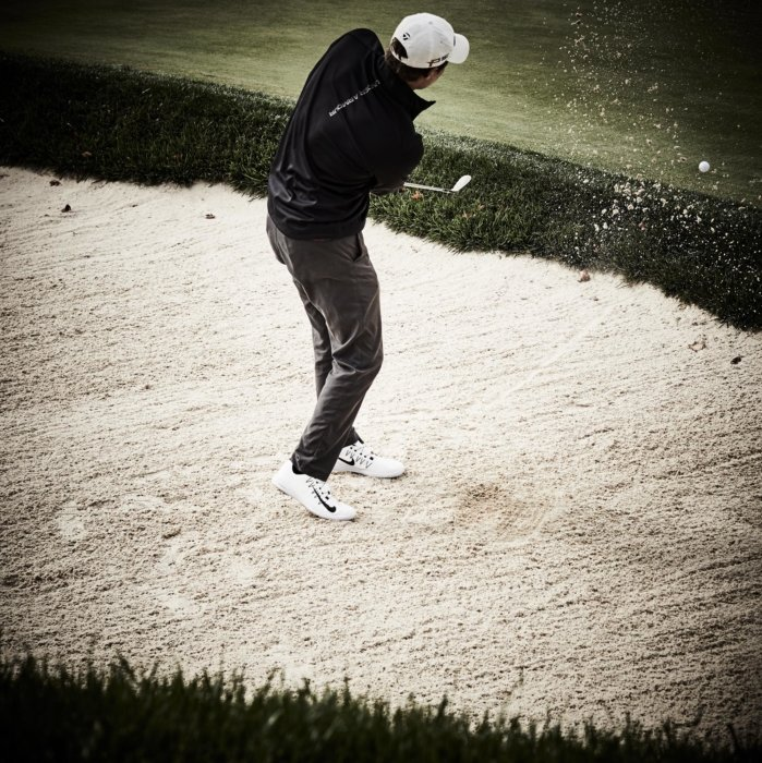 Athletic lifestyle of a golfer in a sandtrap