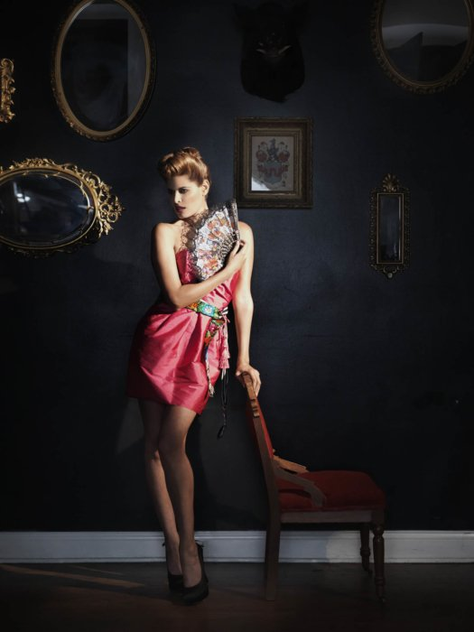 Fashion photography of a woman in a pink dress in a moody house