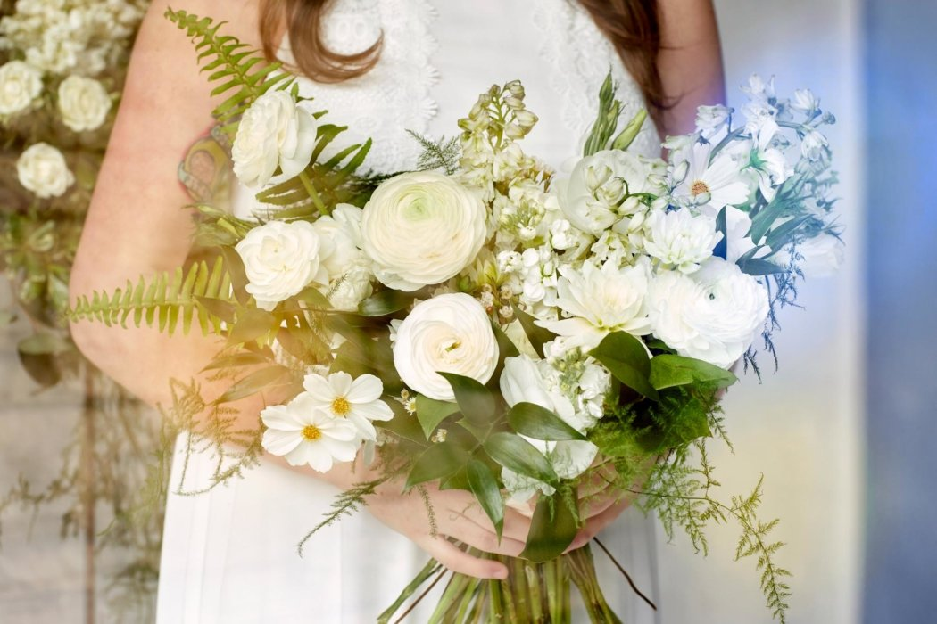 White flowers being held by a woman in a white dress