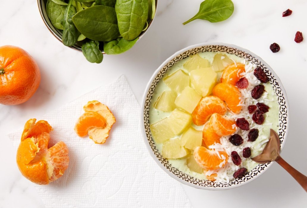 A bowl of fresh fruits and creamy sauce