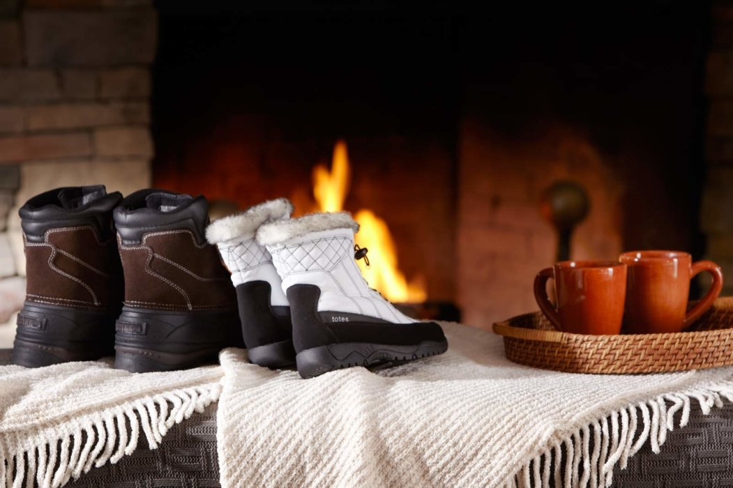 Totes Isotoner shoes by a fire with coffee