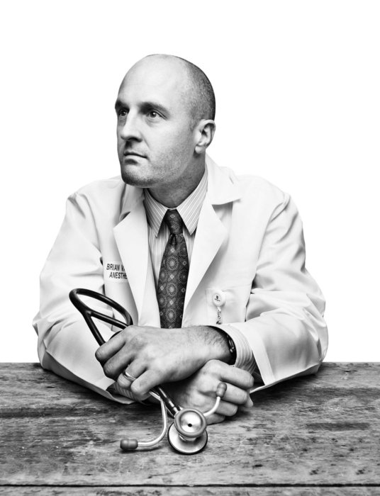 Portrait of a male doctor leaning on a table