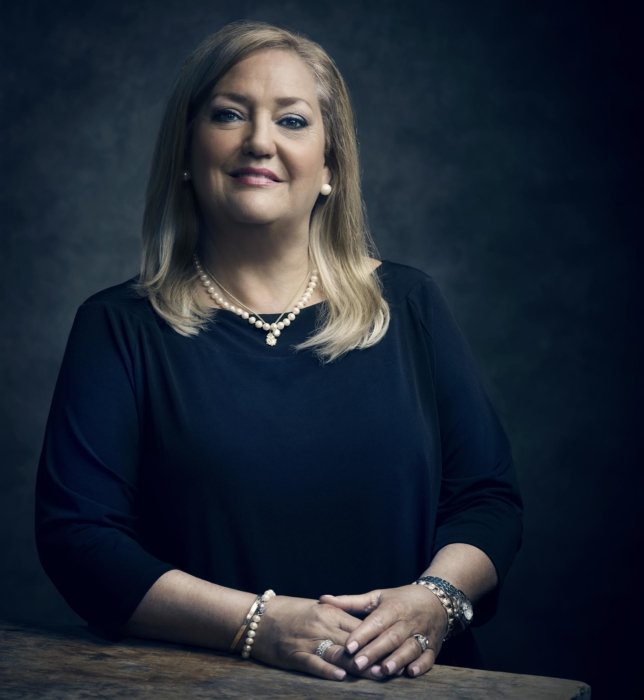 A corporate portrait of woman on a dark background