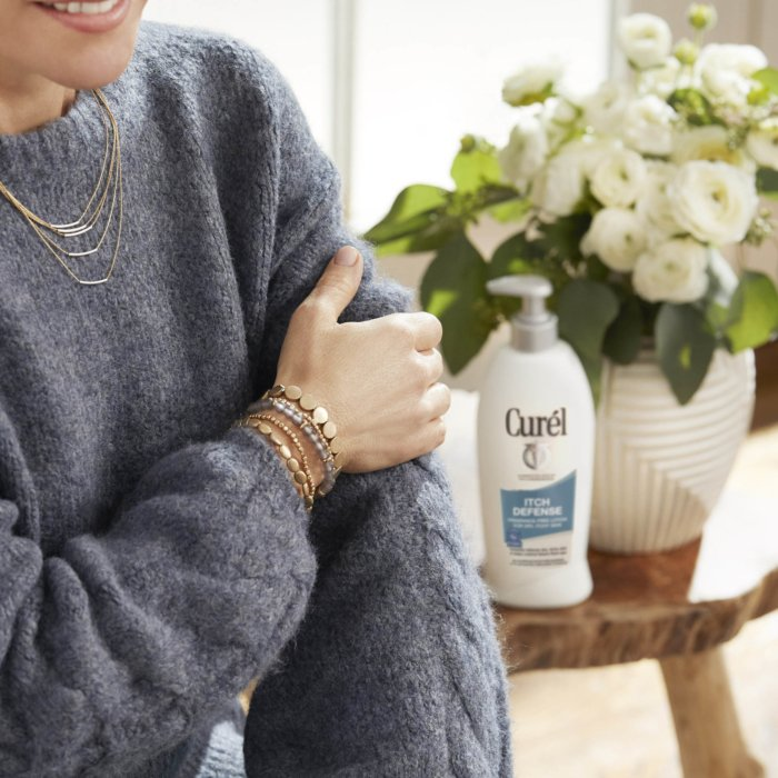 A woman holding her arm with a sweater - with curel product in the back - product photography