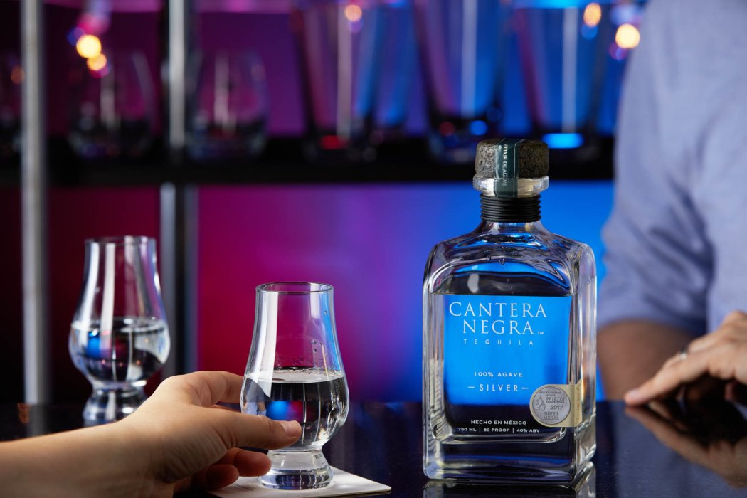 a colorful bar setting with silver tequila - cantera negra - drink photography