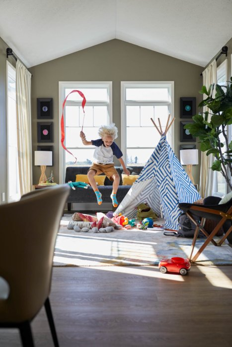 A boy playing with a tent and toys in a modern designed room - lifestyle photography