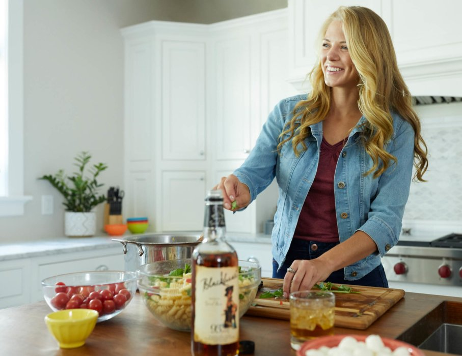 A woman of cooking pizza at a party with blackheart rum - lifestyle drink photography