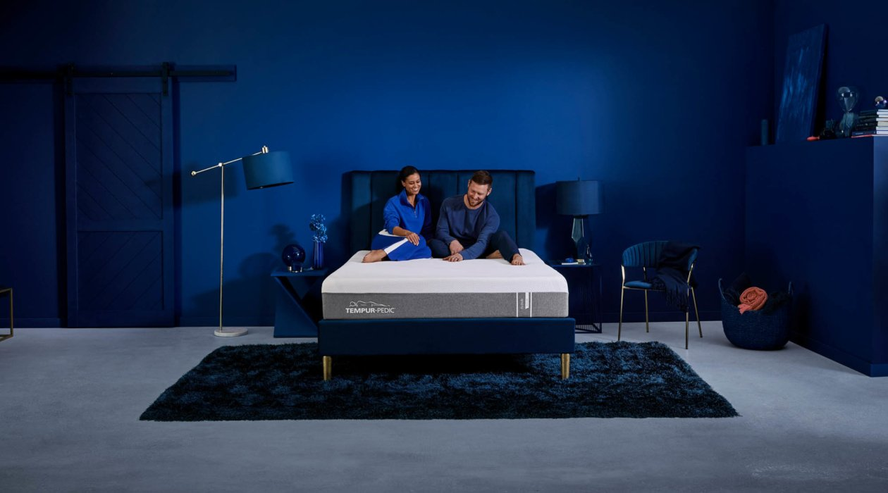 Couple on Tempur-pedic mattress with blue room - - product lifestyle photography