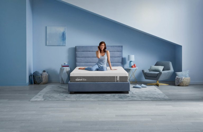 Woman sitting on matress in large room - Tempur-pedic mattress with blue room - - product lifestyle photography