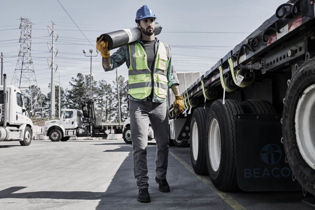 A man working at a job site carrying materials by a truck - work photography
