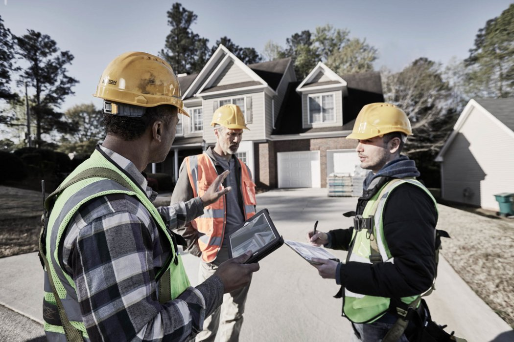 Three men discussing housing plans -- work photography