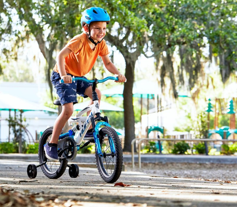 Kid riding huffy bike with training wheels - product lifestyle photography