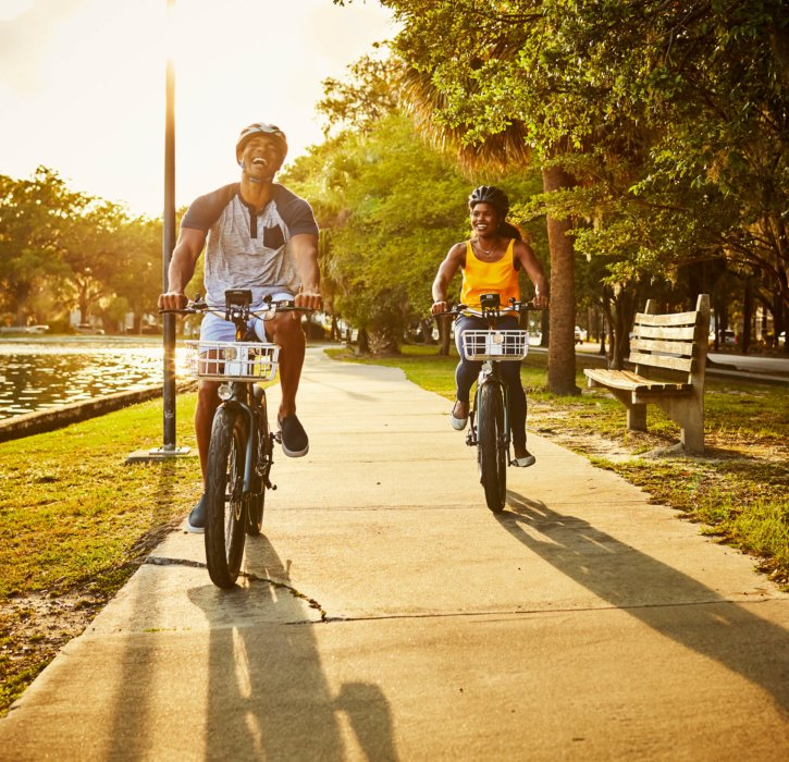 A young couple riding a electric bikes in a city park as dusk - product lifestyle photography