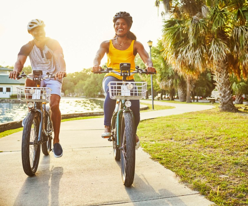 A young couple riding a electric bikes in a city park as dusk by water- product lifestyle photography