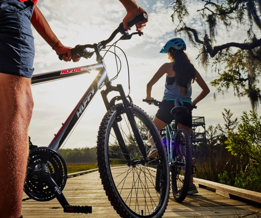 A young couple riding alpine huffy bikes on a water walk way 02 - Royce Union - product lifestyle photography